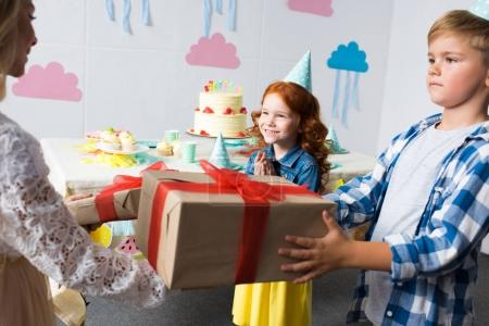 kids presenting gifts to girl