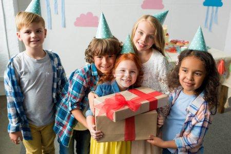 Photo pour Adorables enfants multiethniques heureux tenant des cadeaux d'anniversaire et souriant à la caméra - image libre de droit