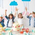 Adorable happy kids raising hands and smiling at camera at birthday table