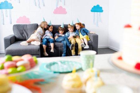 Photo pour Enfants multiethniques utilisant des gadgets tout en étant assis ensemble sur le canapé à la fête d'anniversaire - image libre de droit
