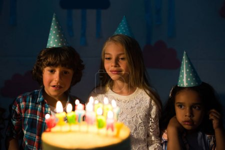 kids looking at birthday cake