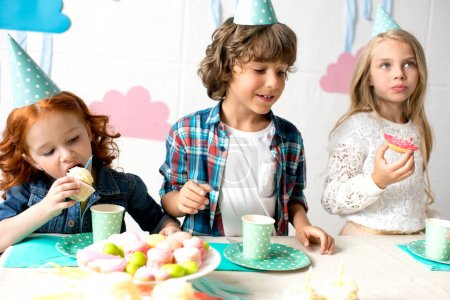 Photo for Adorable little kids in party hats eating delicious sweets at birthday table - Royalty Free Image
