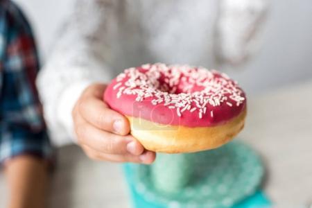 child holding doughnut