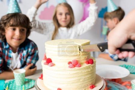 hand cutting birthday cake