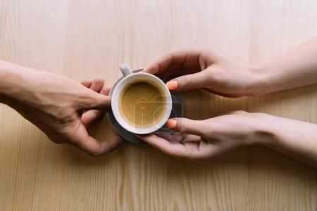 Photo for Top view of hands holding cup of aromatic coffee in cafe - Royalty Free Image