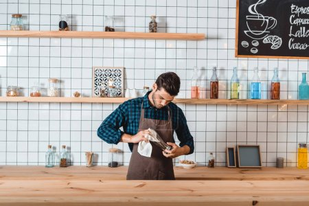 Photo pour Portrait de barista concentré dans le verre de nettoyage de tablier tout en se tenant au comptoir dans le café - image libre de droit