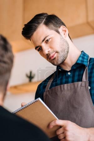 Photo pour Portrait de garçon ciblée en tablier prenant la commande du client dans le café-restaurant - image libre de droit