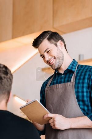 Photo pour Portrait d'un garçon souriant en tablier prenant la commande du client dans le café-restaurant - image libre de droit