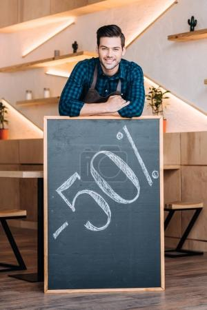 waiter and chalkboard with 50% sale offer