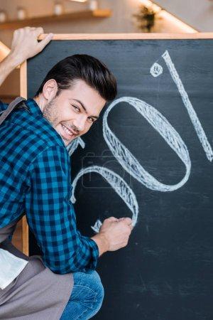 Waiter writing on chalkboard
