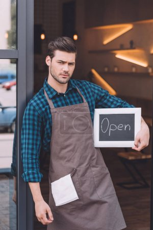 barista holding chalkboard with open word