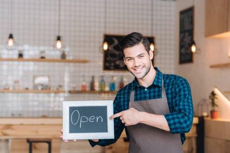 Photo pour Portrait de barista souriant pointant vers le tableau avec mot ouvert à la main dans le café - image libre de droit