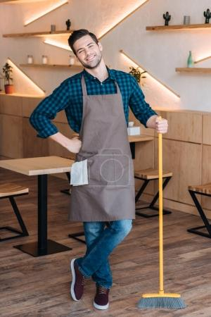 worker with broom in cafe