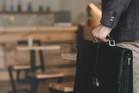 Photo for Cropped shot of businessman holding suitcase in hand in cafe - Royalty Free Image