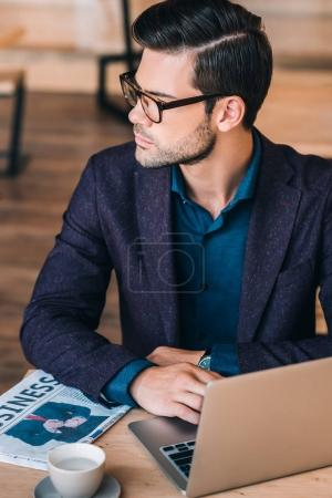 pensive businessman with laptop in cafe
