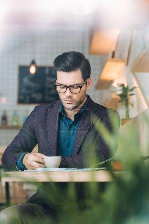 Photo pour Portrait d'un homme d'affaires confiant assis à table avec une tasse de café dans un café - image libre de droit