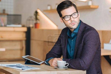 Foto de Retrato de joven empresario pensativo sentado en mesa con taza de café y tableta en café - Imagen libre de derechos