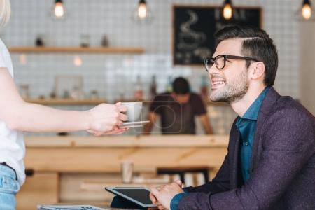 Photo pour Vue latérale d'une serveuse avec commande aux hommes d'affaires dans le café-restaurant - image libre de droit