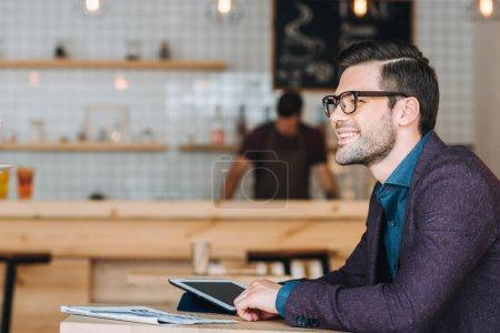 Photo pour Portrait de jeune homme d'affaires souriant assis à table avec journal et tablette dans un café - image libre de droit
