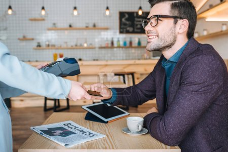 Photo for Side view of smiling businessman paying for cup of coffee with credit card in cafe - Royalty Free Image
