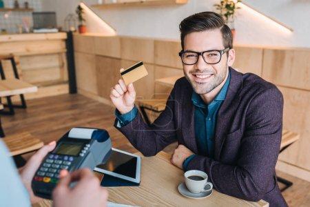 Photo pour Portrait d'homme d'affaires gai payer pour commander par carte de crédit au café - image libre de droit