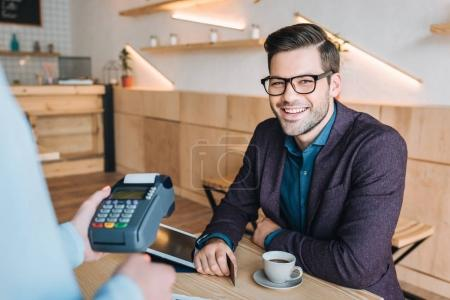 Photo for Portrait of smiling businessman with credit card paying for order in coffee shop - Royalty Free Image