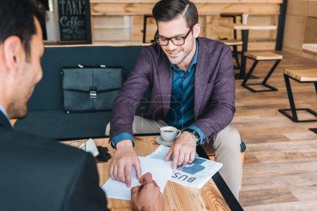 Photo pour Homme d'affaires souriant pointant au contrat ce collègue gestuelle au cours de la réunion au café - image libre de droit