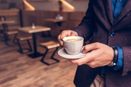 Photo for Partial view of businessman holding cup of coffee in hands in cafe - Royalty Free Image