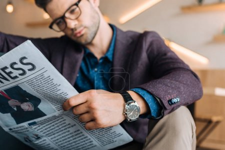 Photo for Selective focus of young businessman reading newspaper while resting in coffee shop - Royalty Free Image