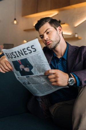 Businessman reading newspaper in coffee shop