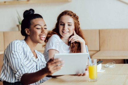 Photo pour Belles filles souriantes multiethniques chantent tablette numérique tout en buvant du jus et du café dans le café - image libre de droit