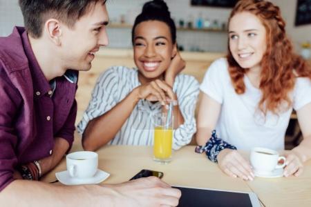 multiethnic friends talking in cafe