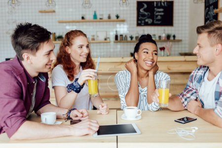 Photo for Happy young multiethnic friends sitting together and talking in cafe - Royalty Free Image