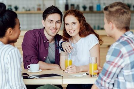 Photo for Happy young couple sitting together and spending time with friends in cafe - Royalty Free Image
