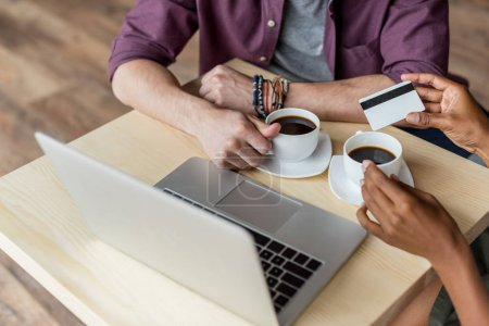 couple with coffee, credit card and laptop