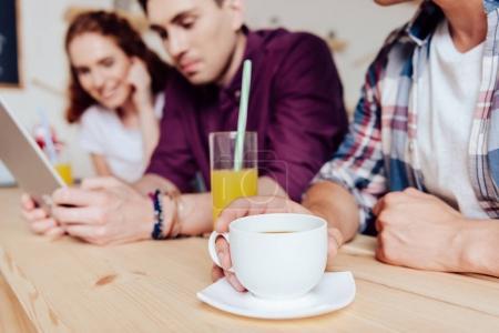Foto de Vista parcial cerca de jóvenes amigos bebiendo café y jugo durante el uso de tabletas digitales en café - Imagen libre de derechos