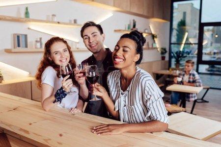 Foto de Felizes amigos multiétnicos joven bebiendo vino y sonriendo a la cámara en el restaurante - Imagen libre de derechos
