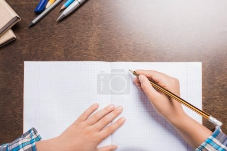 kid writing in notebook