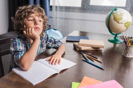 Photo pour Gentil petit garçon à la recherche de suite tout en faisant les devoirs à la maison - image libre de droit