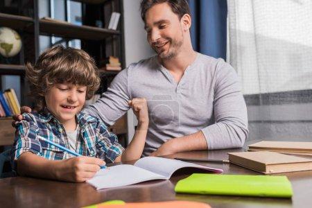 Photo pour Jeune père aidant fils peu souriant à faire leurs devoirs - image libre de droit