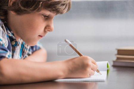 Photo pour Vue latérale d'un petit garçon concentré écrivant dans un copybook assis à table - image libre de droit