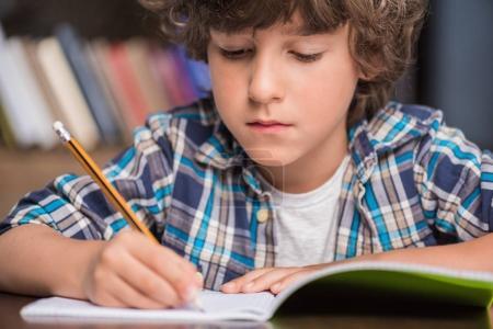 Kid writing in copybook