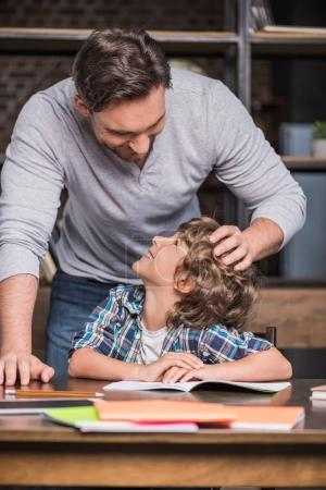 Son doing homework with father