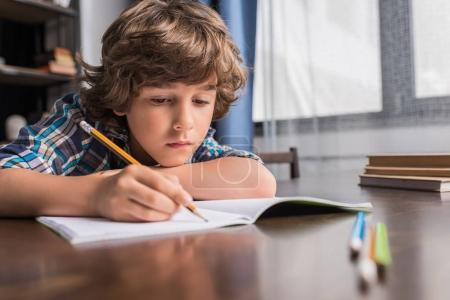 Photo for Portrait of focused little boy writing in copybook while sitting at table - Royalty Free Image