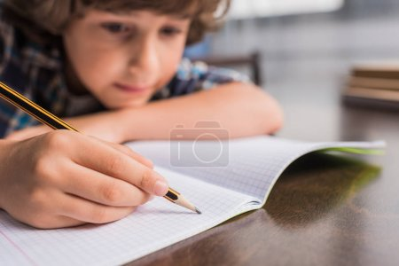 Photo for Selective focus of focused little boy writing in copybook while sitting at table - Royalty Free Image
