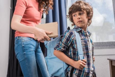 Photo pour Recadrée tir de mère mettre le livre en sac à dos de fils avant l'école - image libre de droit