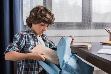 Photo for Side view of caucasian little boy packing backpack for school - Royalty Free Image
