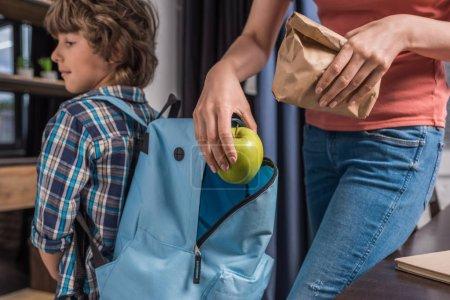 Photo pour Vue partielle de la mère mettant le déjeuner dans le sac à dos fils avant l'école - image libre de droit