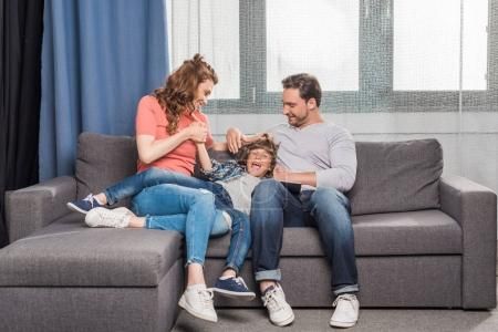 Photo for Happy young family with one child resting on sofa together - Royalty Free Image