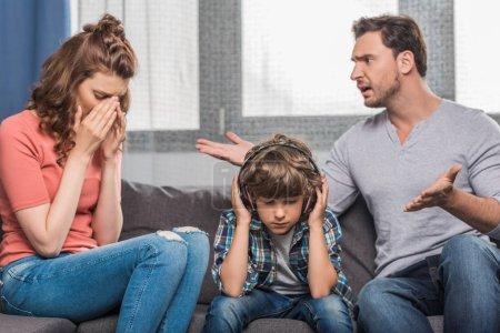Photo pour Parents en soutenant tout petit garçon dans les écouteurs sur les oreilles - image libre de droit